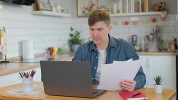 junger Mann liest Papier, während er zu Hause einen Laptop verwendet. fokussierter tausendjähriger Typ, der auf dem Computer beim Surfen im Internet tippt und auf den Bildschirm schaut foto