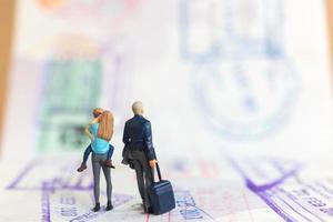 Miniatur-Leute-Paar, das auf einem Pass mit Einreisestempel steht foto