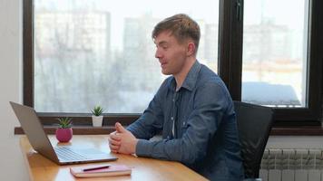 junger Mann, der per Videokonferenz kommuniziert, spricht mit Blick auf den Laptop im Homeoffice, Video-Chat-Fernsprachkurs mit Online-Lehrer foto