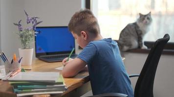 Online-Fernunterricht Unterrichtskonzept. Kinderjunge Kinderschüler mit Lehrer, der Tablet-Laptop-Computer zum Schreiben von Schulhausaufgaben verwendet, zu Hause lernt. foto