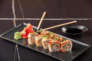Aal-Sushi-Rollen auf schwarzem Hintergrund. Restaurantbedienung foto