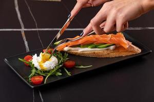 in die Hände geschnittenes pochiertes Ei mit Toast, mit Räucherlachs, Avocado, Tomate und Spinat. foto