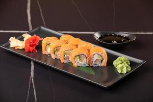 Sushi-Rolle mit Lachs- und Garnelen-Tempura auf schwarzem Hintergrund foto