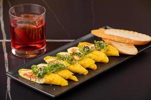 Omelette mit Lachs, Käse und klopft auf einen schwarzen Teller. Keto-Diät-Menü-Konzept. foto