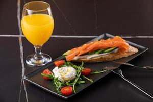 gesundes Frühstück mit Vollkornbrottoast, zerdrückter Avocado, Lachs und pochiertem Ei und Saft foto
