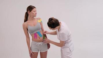 Der Therapeut trägt Kinesio-Tape auf den weiblichen Körper auf. physiotherapeutische und kinesiologische Konzepte. foto