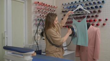 ein Modeschneider bei der Arbeit, der Kleidung mit einem Bügeleisen und Dampf in einer Nähwerkstatt schwebt. Herstellung von Kleidung. Nähprodukte im Bekleidungsgeschäft. foto
