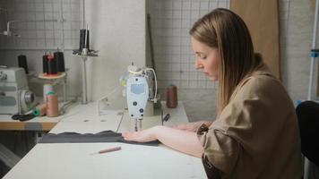 Nahaufnahme einer Schneiderin näht Kleidung, sitzt in der Werkstatt an einem Tisch mit einer Nähmaschine. sie genießt kreatives Arbeiten. Modedesigner, Modegeschäft. foto