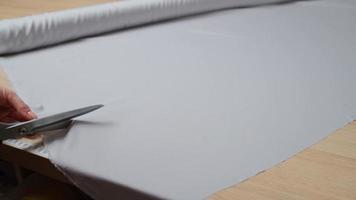 Nahaufnahme von weiblichen Händen, die den Stoff mit einer Schere schneiden. professioneller Schneider, Modedesigner, der im Nähatelier arbeitet. Mode- und Schneiderkonzept foto