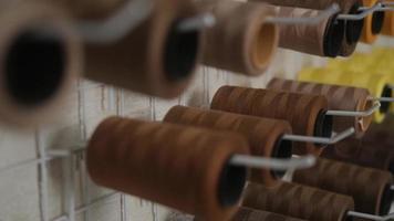 ein Satz farbiger Fäden zum Nähen auf Rollen an der Wand in der Nähwerkstatt. Seitenansicht. foto