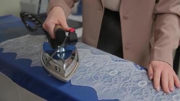Siview kippt mittlere Aufnahme einer Schneiderin, die Spitze dampft, um sie zum Nähen am Bügelbrett in der Werkstatt vorzubereiten foto