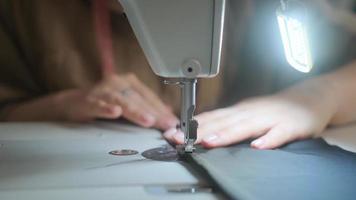 Nähen an der Nähmaschine. Schneider näht auf Nähmaschine. Nahaufnahme der Hand der Frau und des Nähvorgangs. foto