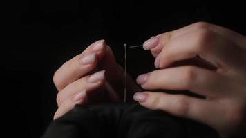 Zeitlupe Schuss von Faden durch die Nähnadel. Frau Nähprojekt von Hand. handgemachte Mode mit hochwertigen Garnen und Stoffen. DIY und schönes Quilten von Modedesigner. Stickerei foto