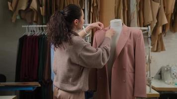 Schneiderin misst Kleidung an Schneiderpuppe mit Maßband. Frau ist konzentriert und nachdenklich. Studio ist hell, modern, mit vielen Nähwerkzeugen und Gegenständen. foto