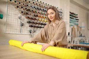 cuaucasianische Schneiderin, die Stoffrolle zum Schneiden von Mustern nimmt. professioneller Modedesigner, der textiles Material misst. Bekleidungsindustrie, Schneiderei, Bekleidungswerkstattkonzept foto