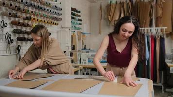 zwei Näherinnen arbeiten mit einem Tuch und einer Kreide auf einem Tisch. Damenschneiderin verwendet Kreide auf der Musterkontur auf Textil, im Atelier. professioneller Schneider, Modedesigner im Nähatelier. foto
