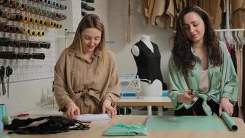 zwei junge erwachsene Modegeschäftsverkäuferinnen in der Studiowerkstatt, die bei einem Online-Geschäftsunternehmen mit zu liefernder Schneiderei arbeiten foto