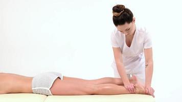 Masseurin massiert die Füße einer jungen Frau auf weißem Hintergrund foto