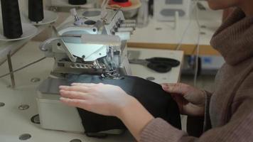 Nähwerkstatt. Verarbeitung der Kante des Produkts auf der Overlock. Zickzack-Maschinenstich. Stofffutter. eine Frau, die an einer Industrienähmaschine näht. Overlock foto