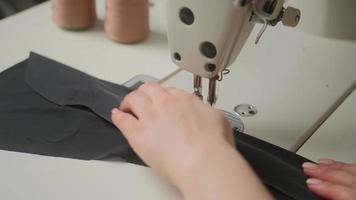 Nähmaschinennadel in Bewegung. Nahaufnahme der Nähmaschinennadel bewegt sich schnell auf und ab. der Schneider näht in der Nähwerkstatt schwarzen Stoff. foto