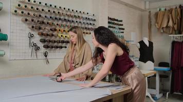 professionelle Schneider, Modedesigner, die im Nähatelier arbeiten. Mode und Schneiderei, Design und Kreativitätskonzept. weibliche Schneider im Werkstattstudio. simstresses schneidet den Stoff. foto