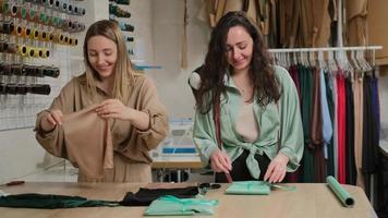 zwei weibliche Schneider, Simstresses oder Modedesigner, die das fertige Produkt in einer schönen Packung zeichnen, die Verkäufer verkaufen die Kleidung in der Werkstatt foto