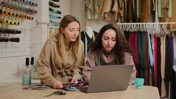 weibliche Schneiderin, die Stoffproben und Fäden zeigt, während sie mit einer Kundin im Nähstudio spricht. Frau hängt Kleider an einem Regal im Hintergrund foto