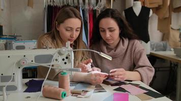 Zwei Modedesigner betrachten Stoffproben in der Nähe einer Nähmaschine in einer Nähwerkstatt foto