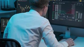 Blick über die Schulter eines Börsenhändlers, der an einem Computer mit mehreren Monitoren arbeitet, die Börsenticker-Nummern anzeigen. foto