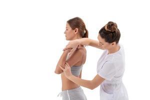Arzt Physiotherapeut streckt eine junge Sportfrau isoliert auf weißem Hintergrund foto