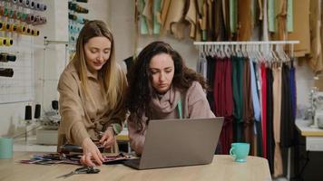 weibliche Schneiderkollegen, die auf den Laptop-Bildschirm schauen, Stoffproben berühren und Farben diskutieren, während sie im Nähstudio zusammenarbeiten foto