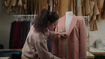 Schneiderin misst Kleidung Anzug bis Schneiderpuppe mit Maßband. Frau ist konzentriert und nachdenklich. Studio ist modern, mit vielen Nähwerkzeugen und Gegenständen. foto