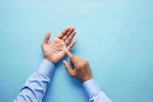 Männerhand mit Medizin aus dem Tablettenbehälter verschüttet foto