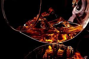 Whisky mit Eis im Glas auf schwarzem Hintergrund isoliert foto
