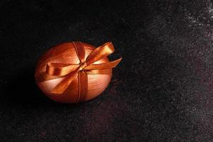 Osterei mit Geschenkband auf dunklem Holzhintergrund foto