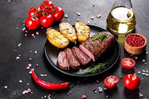 Ribeye Steak mit Kartoffeln, Zwiebeln und Cherrytomaten foto