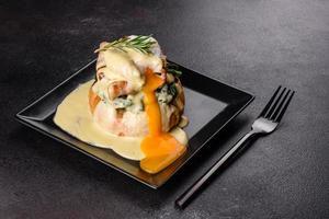 Eier Benedikt oder Eier Florentiner auf einem schwarzen Teller im Café foto