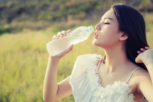 Frau trinkt Wasser für Durst, träumt von weichem Stil. foto
