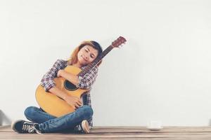 schöne Frau sitzt mit ihrer Gitarre glücklich auf dem Holz sitzend foto