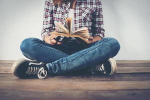 Nahaufnahme von Hipster Frau Hände halten offenes Buch auf Holz sitzend. foto