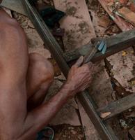 alter älterer Mann, der ein handgefertigtes Holzprodukt mit einem Hammer repariert. foto