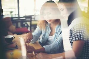 Zwei junge schöne Frauen unterhalten sich in einem Café foto