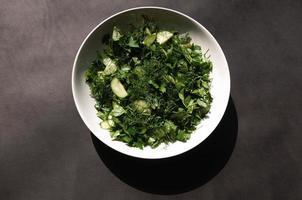 Salat mit Dill und Petersiliengurken auf Teller auf grauem Hintergrund foto