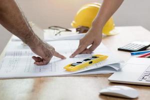Ingenieur oder Architekt, der auf Planpapier auf dem Schreibtisch schaut und zeigt foto