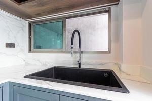 luxuriöses modernes schwarzes Waschbecken auf einer Marmorküchenarbeitsplatte im Haus foto