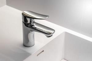 neuer rostfreier Wasserhahn auf sauberem Waschbecken im Badezimmer foto