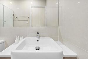 Nahaufnahme kleines Waschbecken und Spiegel im kleinen Badezimmer foto