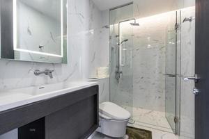 weißes modernes und hölzernes Badezimmer mit Duschkabinenglas in der Wohnung foto