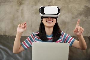 asiatische Frau mit VR-Headset, die die virtuelle 3D-Simulation beobachtet. foto
