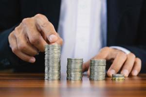 Hand zählende Münzen stapeln sich auf Holztisch foto